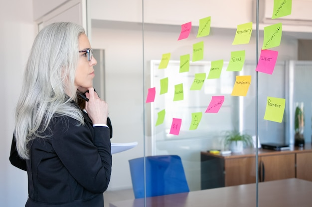 Confident concentrated businesswoman looking at stickers on glass wall. focused grey-haired female worker thinking about notes for project strategy. marketing, business and management concept