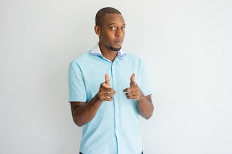 Confident cool African guy pointing at you with finger guns.