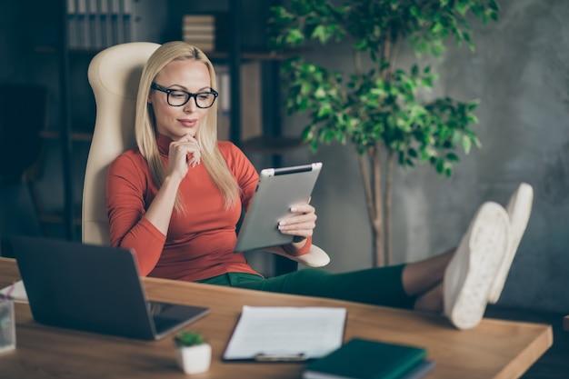 Уверенная в себе крутой лидер, главный владелец компании, женщина, сидящая на стуле, положенная на деревянный стол, использование планшета, чтение новостей о запуске проекта, красная водолазка в офисе рабочей станции