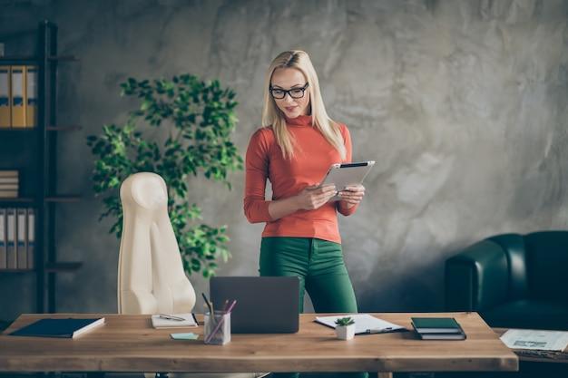 자신감이 멋진 남자 진정한 리더 홀드 태블릿 컴퓨터로보기 현대 시작 정보 스탠드 사무실 로프트에서 오렌지 터틀넥 녹색 바지 바지를 입고