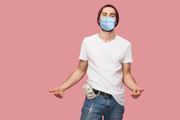 흰 셔츠와 캐주얼 모자를 쓴 외과용 의료 마스크를 쓴 자신감 넘치는 젊은 힙스터 남자, 주머니에 돈을 쥐고 손가락으로 가리키고 있습니다. 실내, 절연, 스튜디오 촬영, 분홍색 배경