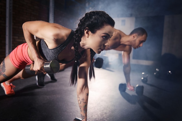 Confident couple working out with dumbbell
