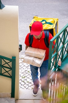 Confident courier delivering order and entering to client yard. deliveryman wearing jeans, red cap and shirt, carrying yellow thermal backpack and carton boxes. delivery service and post concept