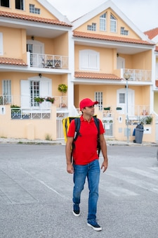 Corriere sicuro che consegna l'ordine e lavora nel servizio postale. fattorino che indossa jeans, berretto rosso e camicia, portando uno zaino termico giallo. servizio di consegna di cibo e concetto di acquisto online