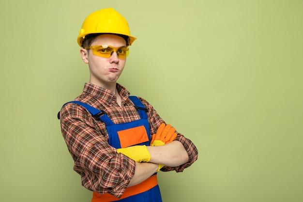 Fiducioso attraversando le mani giovane costruttore maschio indossando uniformi e guanti con occhiali