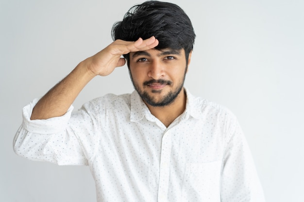 Confident curious young indian man looking into distance and protecting eyes from sun