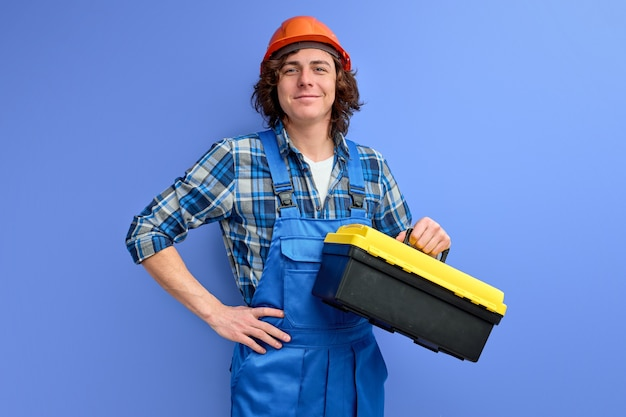 Confident curly caucasian male with tools box for repair isolated on purple wall