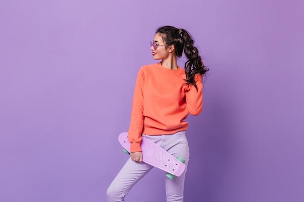 ロングボードを保持している自信を持って巻き毛の韓国人女性。紫色の背景に分離されたスケートボードと魅力的なアジアのモデルのスタジオショット。