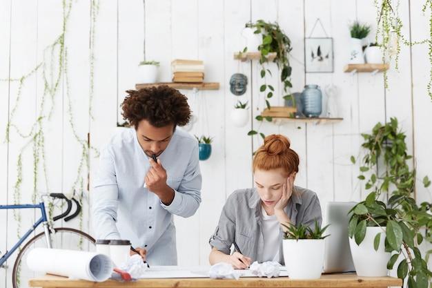 Fiduciosi architetti o ingegneri dalla carnagione scura, uomini e donne dai capelli rossi, brainstorming