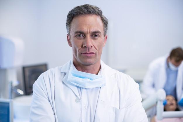Уверенный стоматолог, стоящий в стоматологической клинике