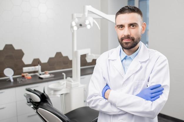 Уверенный стоматолог с бородой, скрестив руки на груди, стоя на рабочем месте