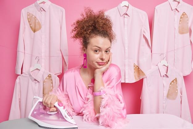 Уверенно решительная кудрявая молодая европейка носит халат, имеет много одежды, гладит позы, возле гладильной доски использует электрическое оборудование. концепция работы по дому и по дому.