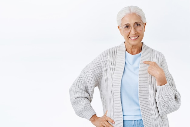 Confident and determined senior woman with grey combed hair in glasses, pointing herself, smiling self-assured, applying for job as nany, motivated and having no doubts she is best, white wall