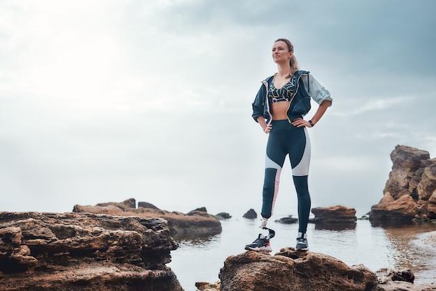 바다 앞 돌 위에 서 있는 생체 공학 다리를 가진 운동복을 입은 자신감 있는 장애인 여성