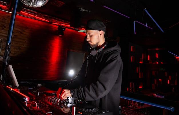 자신감 넘치는 dj는 멋진 나이트 클럽에서 음악을 믹스합니다. 하이테크 개념. 밝은 빨간색 무대 조명과 은색 디스코 공. 재미, 청소년 및 엔터테인먼트 개념.
