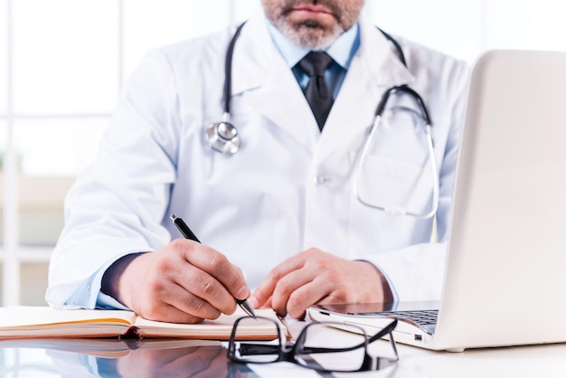 직장에서 자신감 의사입니다. 그의 작업 장소에 앉아있는 동안 메모장에 뭔가를 쓰는 성숙한 의사의 클로즈업