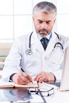직장에서 자신감 의사입니다. 직장에 앉아 있는 동안 메모장에 무언가를 쓰는 성숙한 회색 머리 의사
