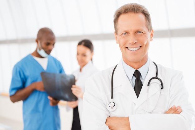 自信のある医者。彼の同僚がバックグラウンドでx線について話している間、腕を組んで笑顔を保つ陽気な成熟した医師