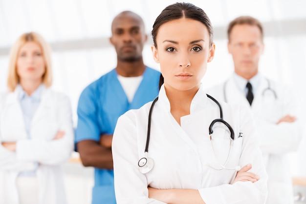 彼女のチームを率いる自信のある医者。彼女の同僚がバックグラウンドで彼女の後ろに立っている間、腕を組んでカメラを見ている美しい女性医師