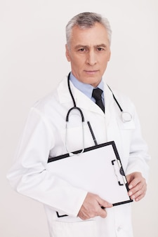 Confident doctor. senior grey hair doctor in uniform looking at camera and holding a clipboard in his hands while standing isolated on white
