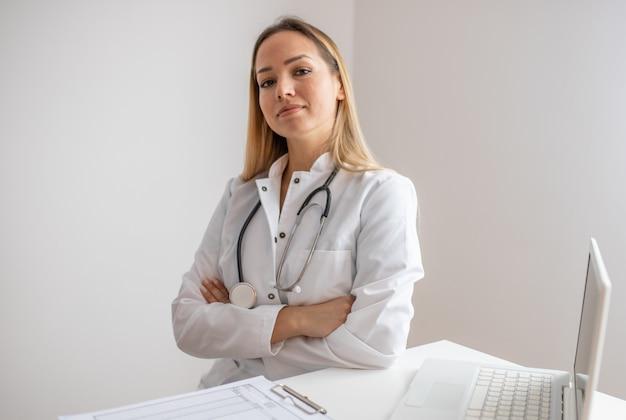 自信を持って医師がオフィスに座っています。