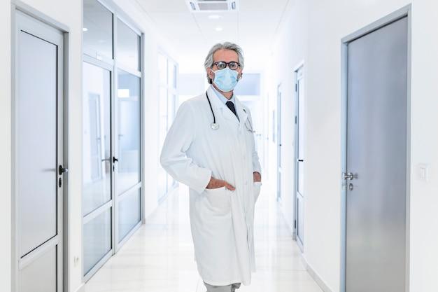 病院の廊下に立っている間保護フェイスマスクを身に着けている自信のある医師