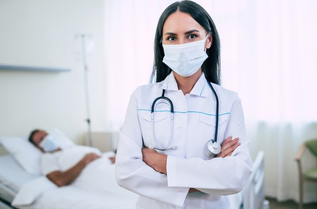 A confident doctor woman in a safety medical mask is examining a mature patient in the mask while he lying in the ward.
