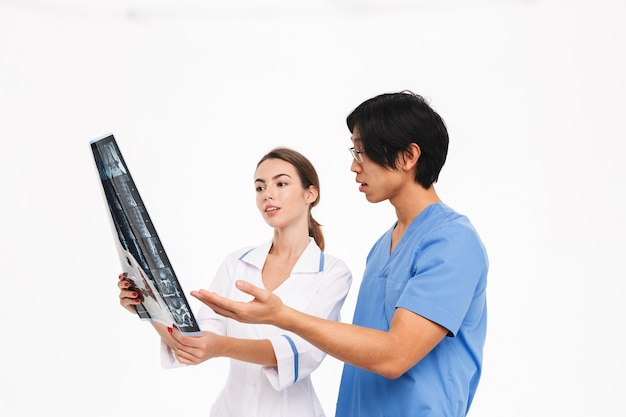 Confident doctors couple wearing uniform standing isolated over white wall, examining x-ray photograph