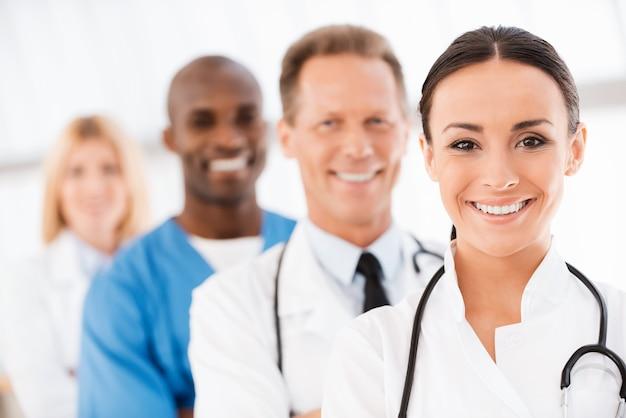 自信のある医師チーム。彼女の同僚が彼女の後ろに並んで立っている間、カメラを見て微笑んでいる自信のある女性医師