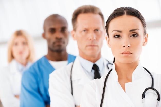 自信のある医師チーム。彼女の同僚が彼女の後ろに並んで立っている間、カメラを見ている自信のある女性医師