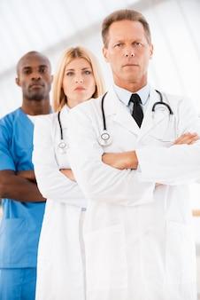 자신감 의사 팀입니다. 카메라를 보고 팔짱을 끼고 있는 자신감 있는 남성 의사는 그의 동료들이 그의 뒤에 줄지어 서 있는 동안
