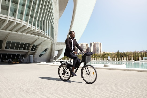 Confident eco friendly dark-skinned ceo using two wheeled pedal assist vehicle to get to work. successful modern black businessman riding bicycle to office after lunch . people, transport and business