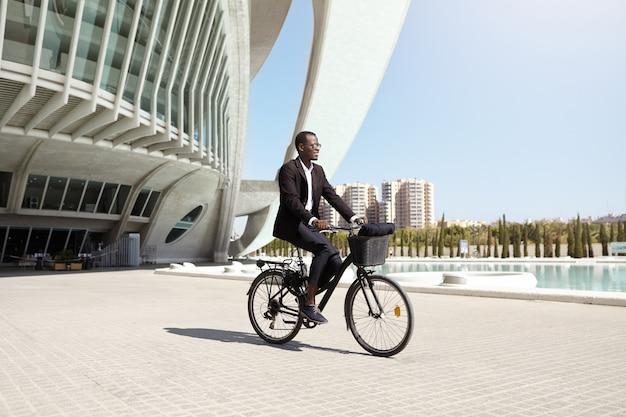 Уверенный экологичный темнокожий генеральный директор, использующий двухколесную педаль, помогающую автомобилю, чтобы добраться до работы. успешный современный черный бизнесмен езда велосипедов в офис после обеда. люди, транспорт и бизнес