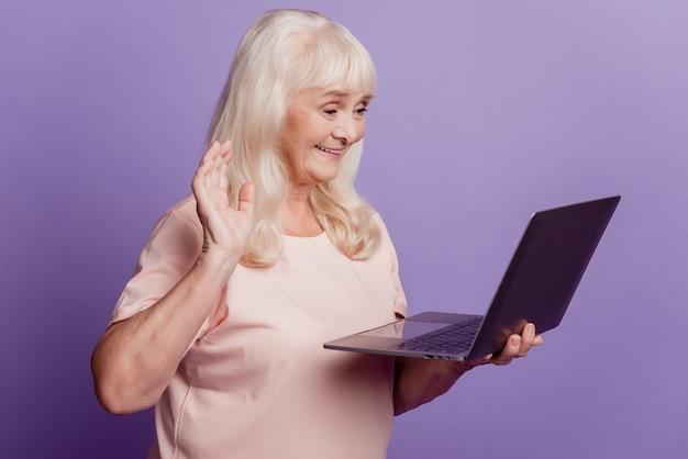 Уверенно старшая женщина держит ноутбук, разговаривает с видеозвонком, волна рукой, приветствует, изолирована на фиолетовом фоне