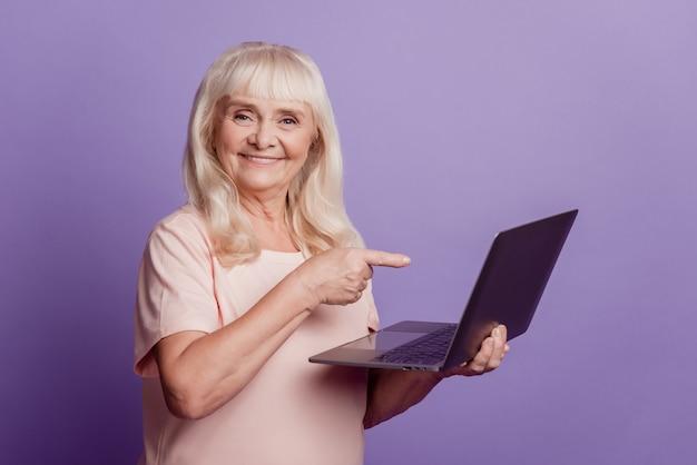 Уверенно старшая женщина держит ноутбук с указательным пальцем, изолированным на фиолетовом фоне