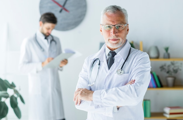 Confident elderly doctor in office
