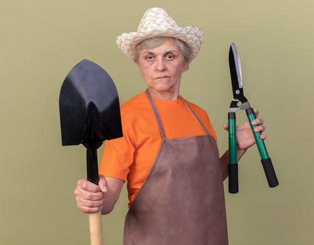 コピースペースのあるオリーブグリーンの壁に隔離されたガーデニングはさみとスペードを保持しているガーデニング帽子を身に着けている自信を持って年配の女性の庭師