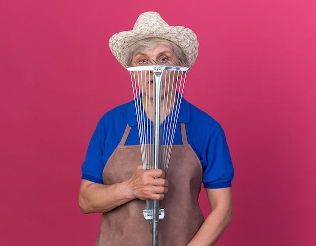 핑크에 잎 갈퀴를 들고 원예 모자를 쓰고 자신감 노인 여성 정원사