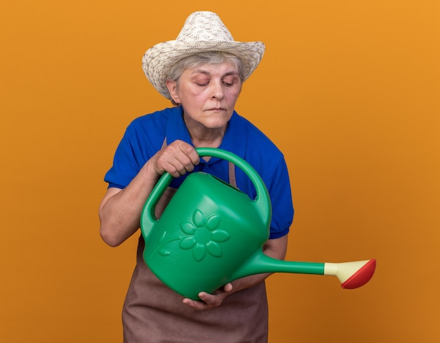 Confident elderly female gardener wearing gardening hat holding and looking at watering can