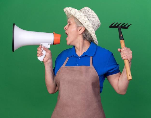 원예용 모자를 쓰고 갈퀴를 들고 큰 스피커에 대고 외치는 자신감 있는 노년 여성 정원사는 복사 공간이 있는 녹색 벽에 고립된 쪽을 바라보고 있습니다.