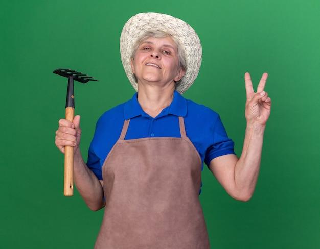 Fiducioso giardiniere donna anziana che indossa cappello da giardinaggio tenendo rastrello e gesticolando segno di vittoria
