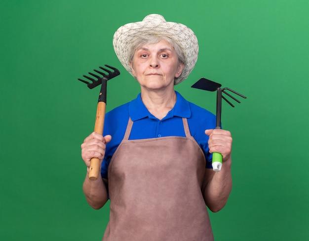 Fiducioso donna anziana giardiniere che indossa cappello da giardinaggio che tiene rastrello e rastrello zappa