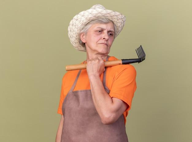 복사 공간이 있는 올리브 녹색 벽에 격리된 면을 바라보는 어깨에 갈퀴를 들고 정원 가꾸기 모자를 쓴 자신감 있는 노인 여성 정원사