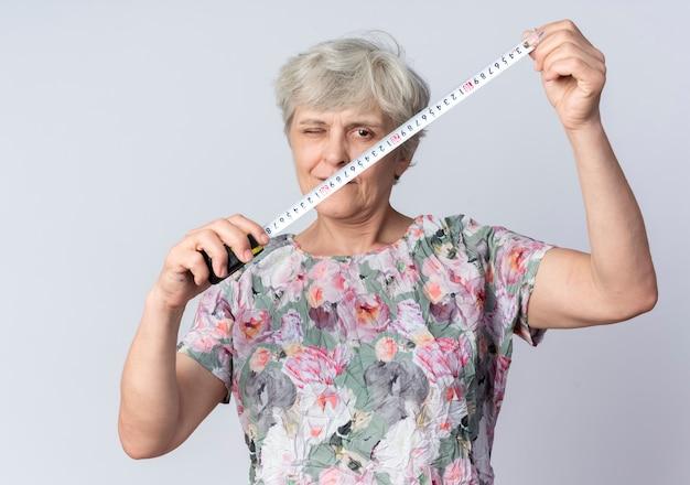 自信を持って年配の女性が目を瞬き、白い壁に巻尺を保持します。