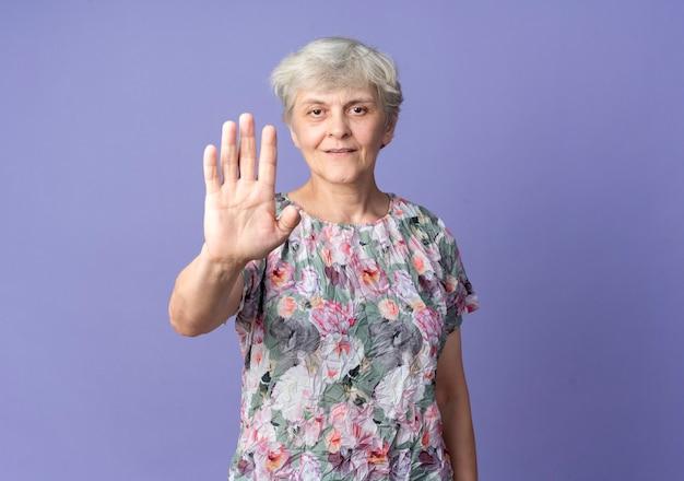 Уверенная пожилая женщина жестами останавливает знак рукой, изолированную на фиолетовой стене