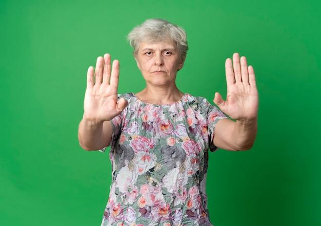 Уверенная пожилая женщина жестами останавливает знак рукой с двумя руками, изолированными на зеленой стене