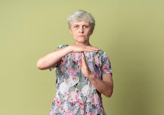 自信を持って年配の女性のジェスチャーは、オリーブグリーンの壁に分離された手のサインをタイムアウトします