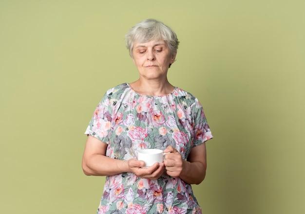自信を持って年配の女性は、オリーブグリーンの壁に隔離されたカップを保持し、