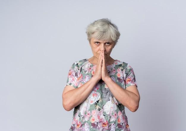 La donna anziana sicura tiene le mani insieme vicino alla bocca isolata sulla parete bianca
