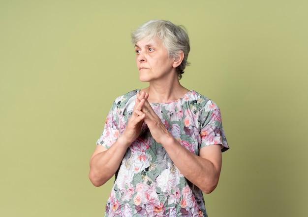 自信を持って年配の女性がオリーブグリーンの壁で隔離の手を一緒に保持
